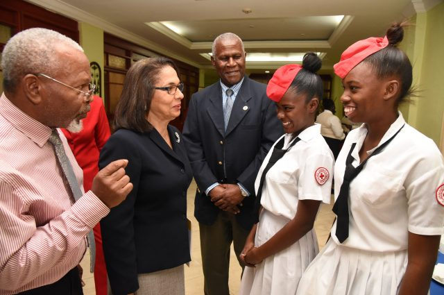 Minister of Labour and Social Security, Hon. Shahine Robinson (second left); Chairman, Jamaica Red Cross 70th Anniversary Committee, Silvera Castro (left); and President, Jamaica Red Cross, Dr. Dennis Edwards (centre), interact with students of Bridgeport High School, Kadian Smith (second right) and Natasha Morrison, during the media launch of the Jamaica Red Cross 70th Anniversary celebration, at The Knutsford Court Hotel in New Kingston on February 16.